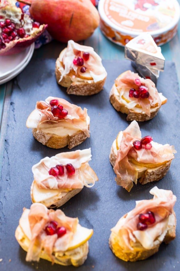 Prosciutto, Pear, Pomegranate and Cheese Crostini from The Girl In The Little Red Kitchen | Quick and easy snack of sweet, salty and creamy with The Laughing Cow cheese.