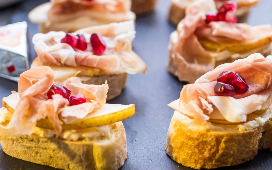Prosciutto Pear Pomegranate and Cheese Crostini