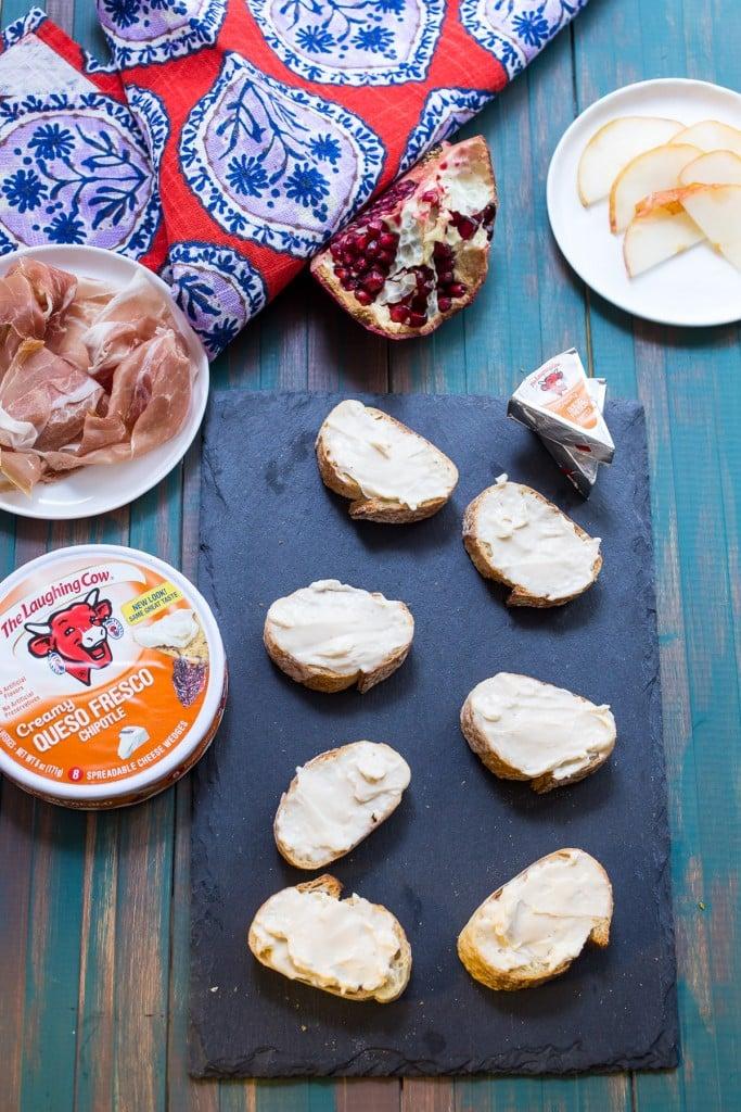 Prosciutto, Pear, Pomegranate and Cheese Crostini   girlinthelittleredkitchen.com