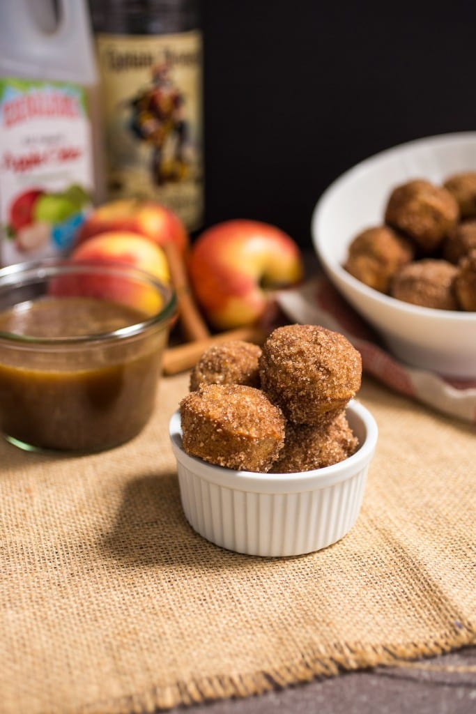 Apple Cider Donut Holes with Hot Buttered Rum Dipping Sauce from The Girl In The Little Red Kitchen | Keep your kitchen clean with these baked cider donuts and boozy spiked dipping sauce!