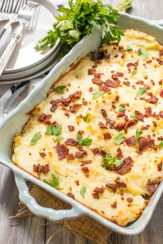 Twice Baked Potato Casserole from The Girl In The Little Red Kitchen | Make-ahead casserole with creamy, cheesy and bacon topped potatoes to serve a crowd.